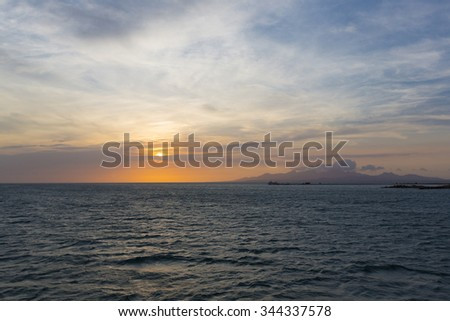 Colorful ocean beach sunset with deep blue sky and sun rays on the harbor of Margarita, Venezuela. - stock photo
