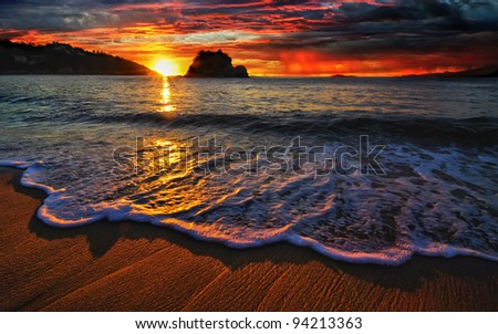Colorful ocean sunrise with breaking wave - stock photo