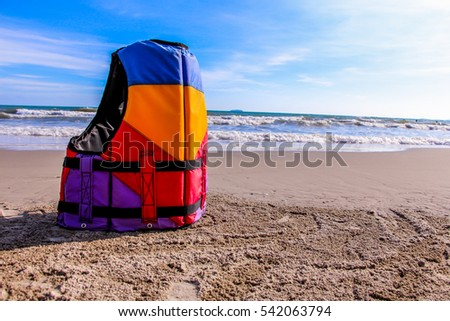 Colorful of Life jackets placed on the beach background of sea in summer time.