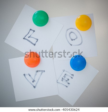 Colorful of Magnet paper clip text is love on gray refrigerator background, abstract background. - stock photo