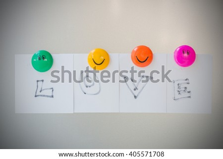 Colorful of smile Magnet paper clip text is love on gray refrigerator background, abstract background. - stock photo
