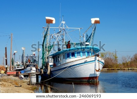Colorful old wooden shrimp boat trawlers docked along Bayou Lafourche in South Louisiana.