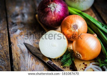 colorful onions on rustic wooden background - stock photo