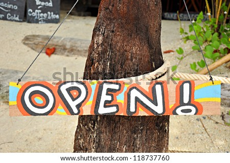 Colorful open sign on the beach - stock photo