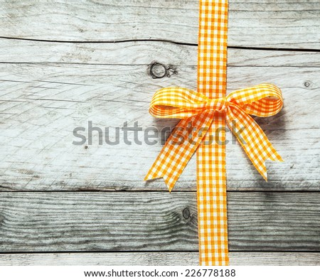 Colorful orange and white festive rustic ribbon and bow decorating a background of old cracked weathered wooden boards with copyspace for your seasonal Christmas or birthday message - stock photo
