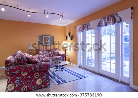 Colorful orange livingroom with french doors - stock photo