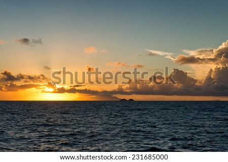 Colorful orange tropical ocean sunset lighting up the horizon and sky over a calm blue sea with scattered cloud - stock photo
