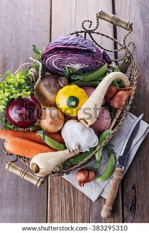 Colorful organic vegetables in vintage a metal basket over rustic wooden background