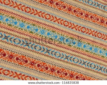 Colorful ornamented woolen textile close up in beige, orange, blue and azure. - stock photo