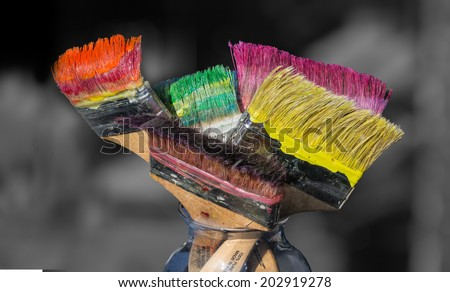 Colorful paint brushes full of paint - stock photo