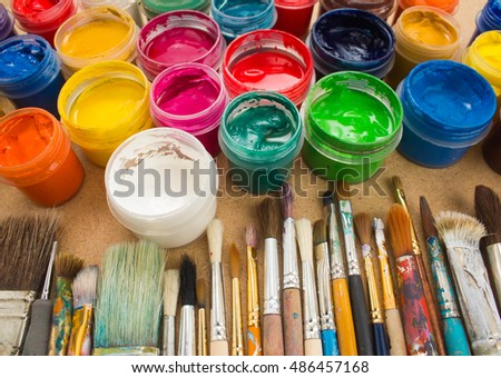 Colorful paint, brushes on wood background