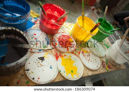 Colorful paint buckets with color spots on the table  - stock photo