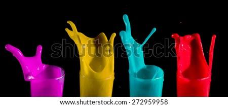 Colorful paint splashing on black background - stock photo