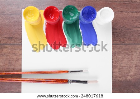 Colorful paint strokes with brush and paint cans on white sheet of paper on wooden table background - stock photo