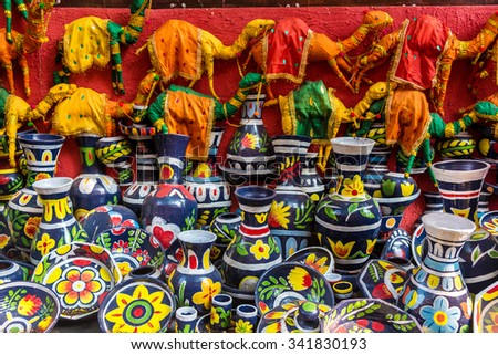 Colorful painted clay vases, pots and toy camels for sale at a street market in India