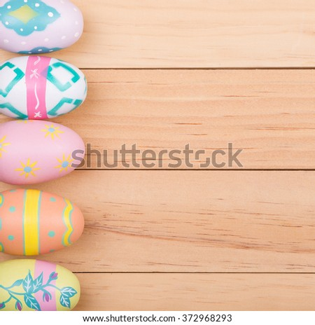 Colorful painted Easter eggs on wood background