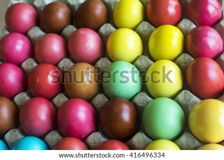 Colorful painted eggs in a tray for sale.