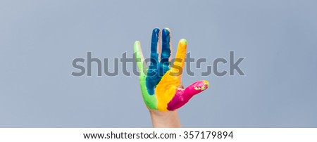 Colorful painted hand and fingers on blue background.
