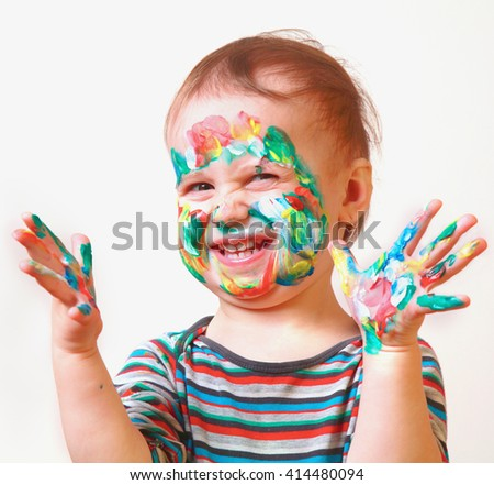 Colorful painted hands in a beautiful young smiling girl - stock photo