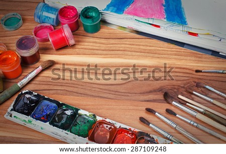 Colorful paints and brushes arranged as a frame on wooden table - stock photo
