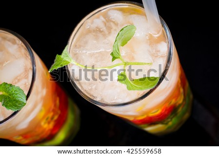 Colorful pair of cocktail drinks with fruit and straws on dark table with blue background - stock photo