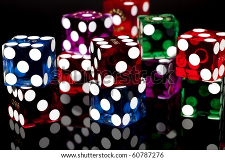 Colorful pairs of casino gaming/gambling dice isolated on a black background with reflection. - stock photo
