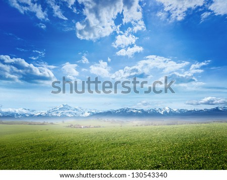 Colorful panorama of green field with blue sky - stock photo