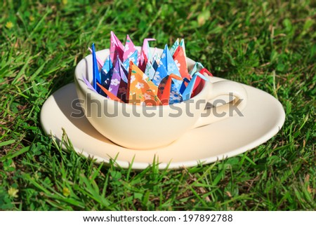 Colorful paper birds in a cup on the grass - stock photo