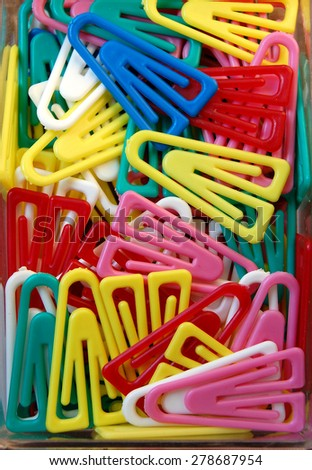 Colorful paper clips in a plastic box - stock photo