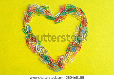Colorful paper clips in the shape of a heart isolated on a yellow background - stock photo
