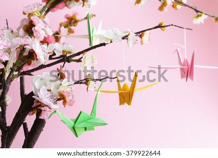 colorful paper origami birds on flowering branches of cherry (sakura) - stock photo