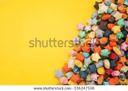 Colorful paper stars on yellow background with room for text
