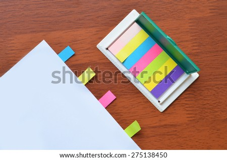 Colorful paper stick marker on the white blank paper - stock photo