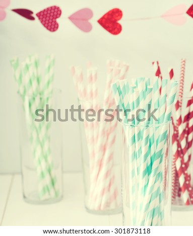 Colorful paper straws with a decorative garland of hearts symbolic of love to celebrate a party for a festive romantic occasion - stock photo