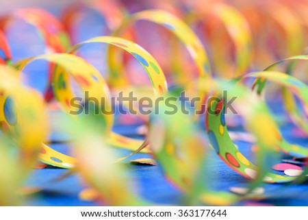 colorful paper streamer at carnival party over blue background