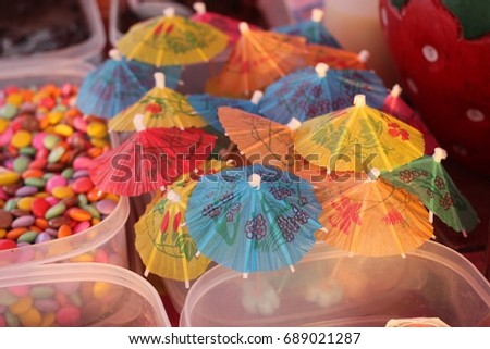 Colorful paper umbrellas topping of dessert