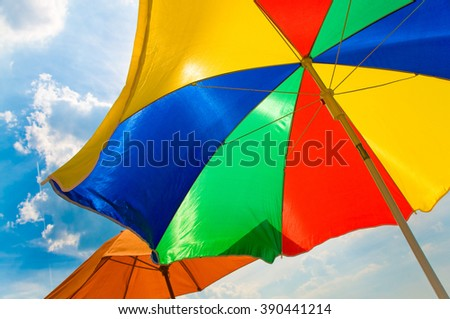 Colorful parasol on blue sky with clouds; Primary colors; Protection against sunlight; Sun shading - stock photo