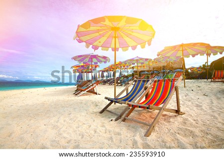 Colorful parasols on a tropical island beach. - stock photo