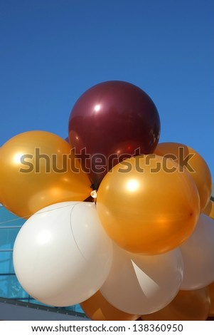 Colorful party balloons are strung together floating into a clear blue sky