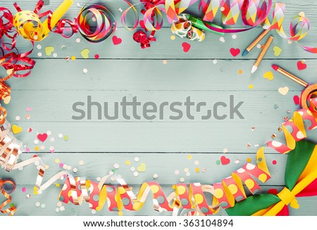 Colorful party frame with streamers and confetti and a vibrant bow tie in a corner around central copy space on a rustic wooden background - stock photo