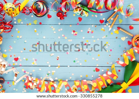 Colorful party streamer and bow tie border on a rustic blue wood background with central copyspace with scattered multicolored paper confetti - stock photo