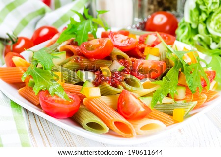 Colorful pasta on a white plate on a wooden - stock photo