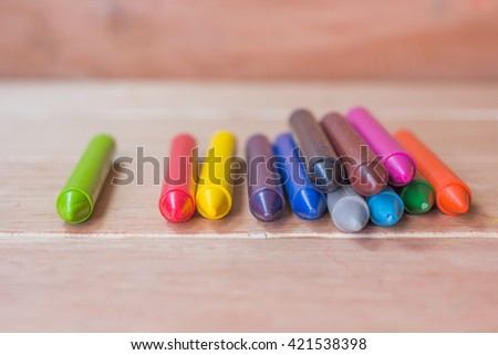Colorful pastel crayons on wooden background
