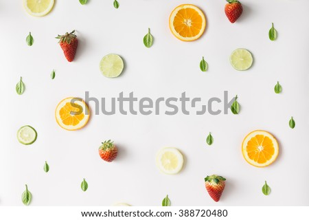 Colorful pattern made of citrus fruits, leaves and strawberries - stock photo