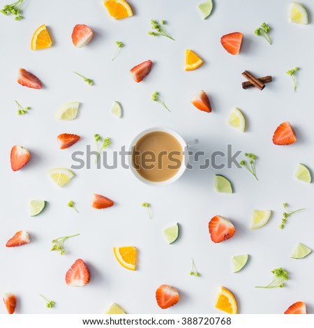 Colorful pattern made of citrus fruits, leaves and strawberries with cup of coffee or tea. - stock photo