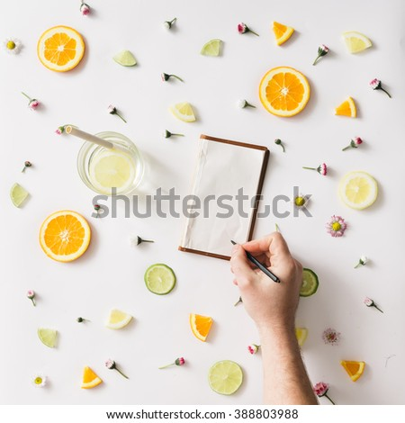 Colorful pattern made of orange, lemon, lime and flowers with hand writing on old notebook. - stock photo