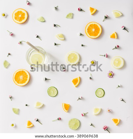 Colorful pattern made of orange, lemon, lime and flowers with lemonade. - stock photo