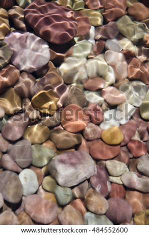 Colorful pebbles as see through clear water