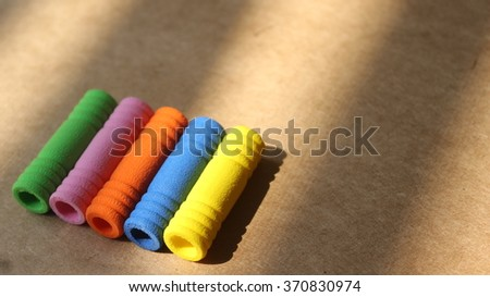 colorful pen and pencil grip on brown background