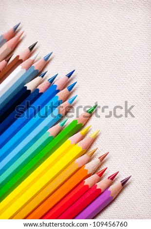 Colorful pencil crayons on the background fabric - stock photo